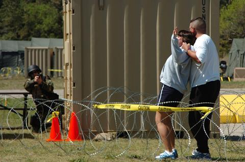 A sailor simulating a crazed husband holds a gun on his wife during a training exercise